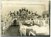 Gent: Koningin Maria Hendrikaplein: Flandria Palace Hotel (Duits krijgshospitaal): groepsportret van verpleegde Duitse soldaten, artsen en verpleegkundigen in een ziekenzaal, 1916