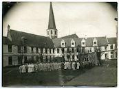 Gent: Antonius Triestlaan 12 / Ekkergemstraat: Militair hospitaal of Krijgsgasthuis, oud Klooster van Deinze (Duits krijgshospitaal): tuin met groepsfoto van Duits personeel en verpleegden met op de achtergrond de kloostervleugels voor de Sint-Martinuskerk van Ekkergem, 1915-1916
